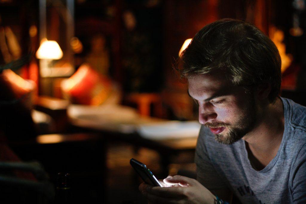 Mies katsoo älypuhelinta ravintolan pöydässä