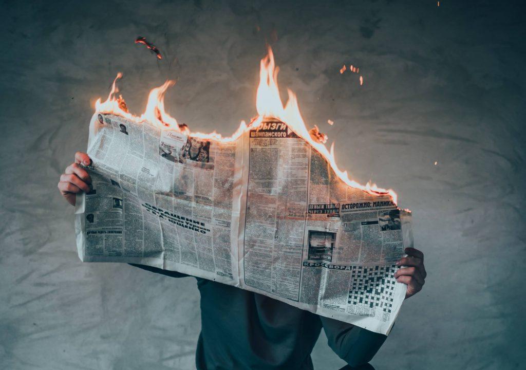 Henkilö lukemassa sanomalehteä, joka palaa.