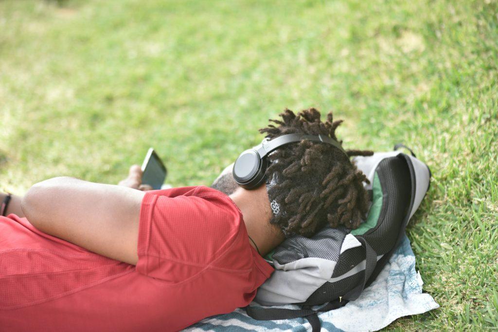 Mies makoilee puistossa puhelin kädessään