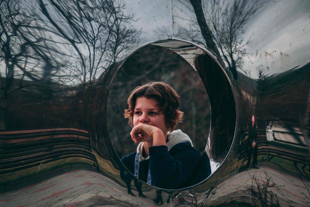 Lapsi, joka näkyy heijastavassa pinnassa olevasta ikkunasta