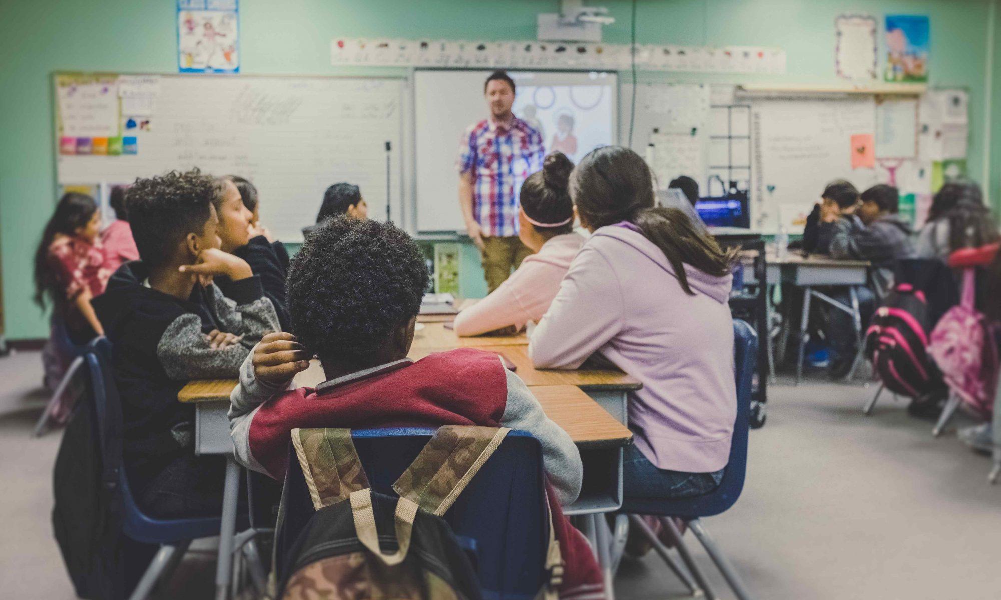 Luokkahuone, jossa lapsia pienryhmissä ja opettaja