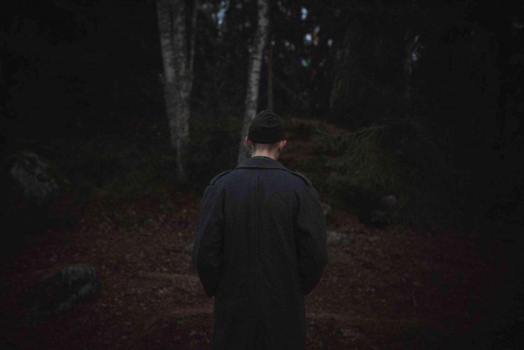 Mustiin pukeutunut henkilö synkässä metsässä.