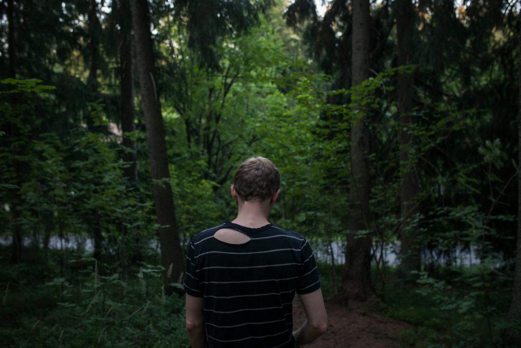 Ihminen kesäisessä metsässä takaapäin kuvattuna