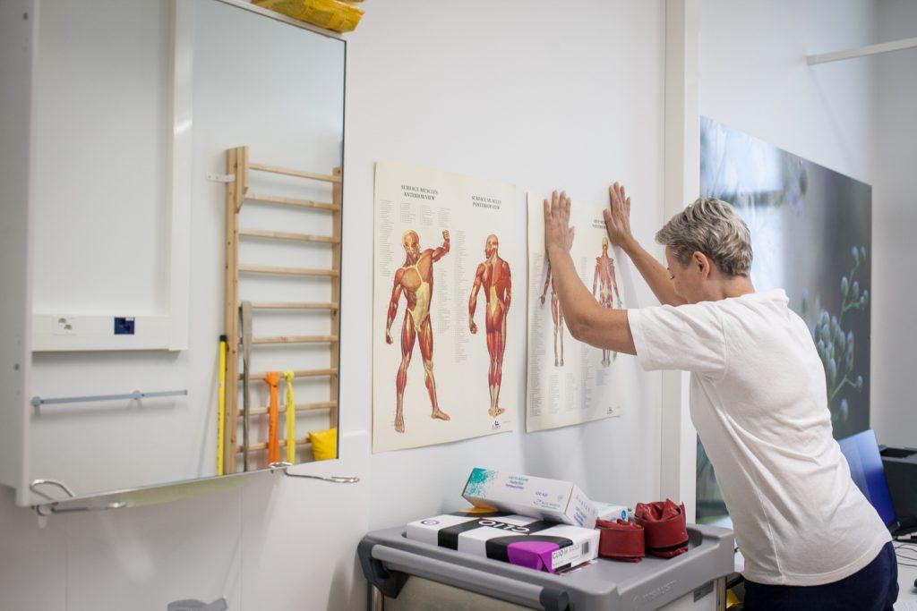 Henkilö painaa käsiään seinää vasten. Seinällä on kuvia ihmisen lihaksistosta.