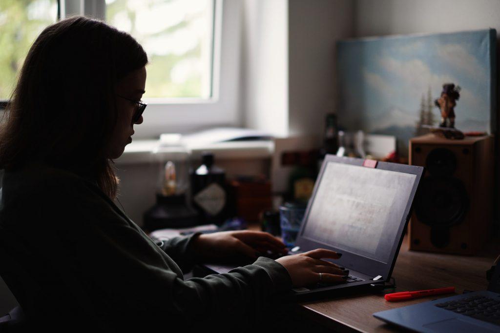 Pitkätukkainen hahmo käyttää kannettavaa tietokonetta pöydän ääressä