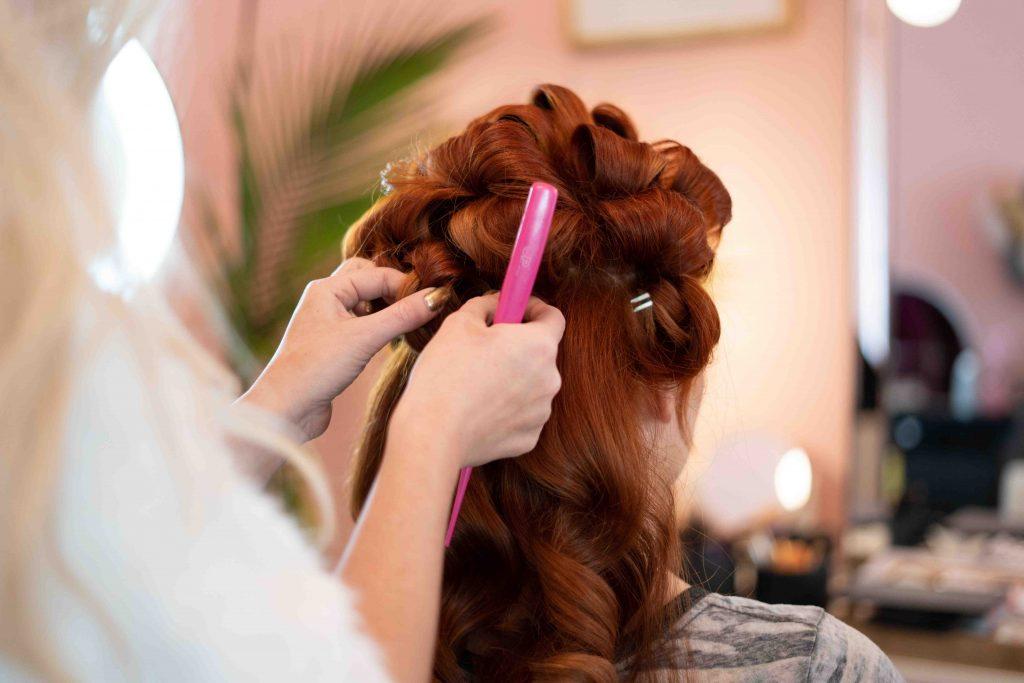 Kampaaja laittaa kiharoita pitkiin, punaisiin hiuksiin