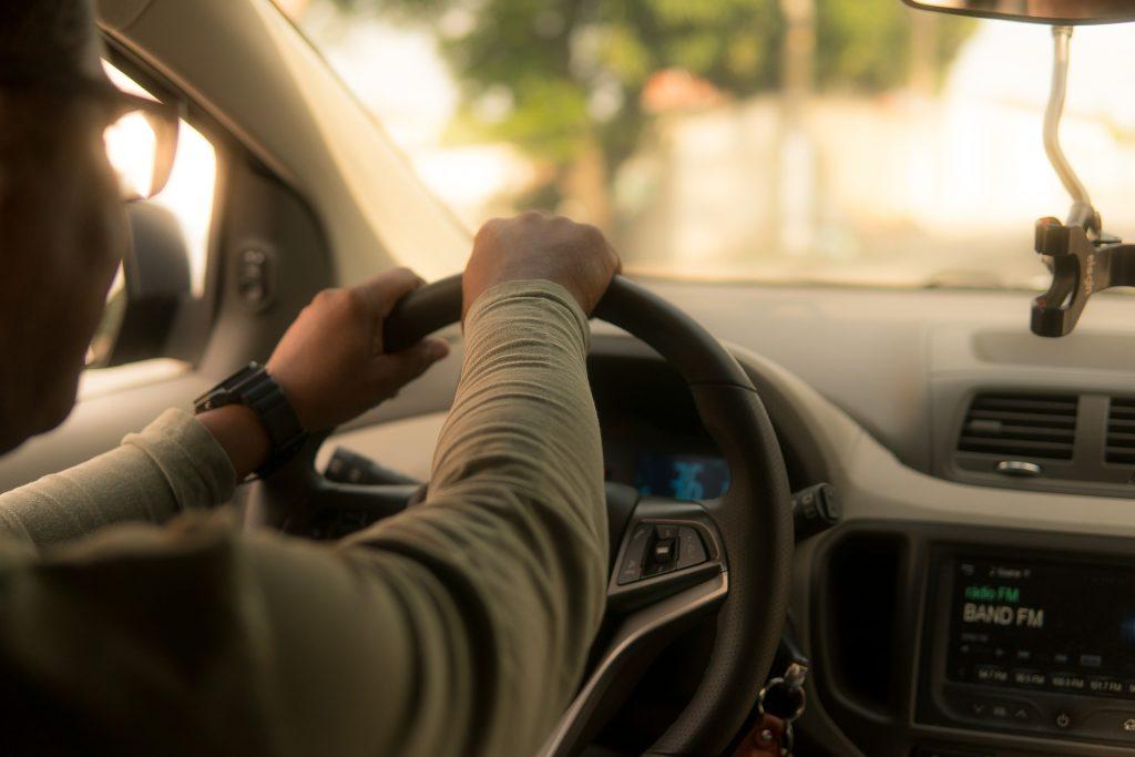 Kädet auton ohjauspyörällä