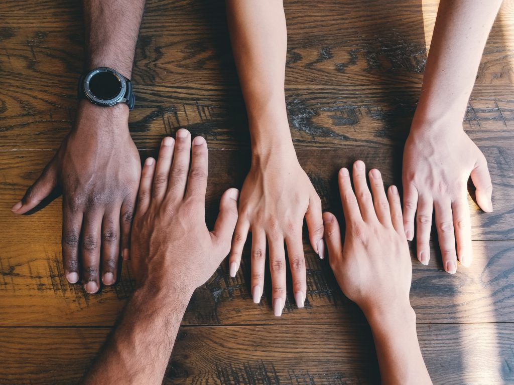 Ihmisten käsiä rinnakkain pöydällä