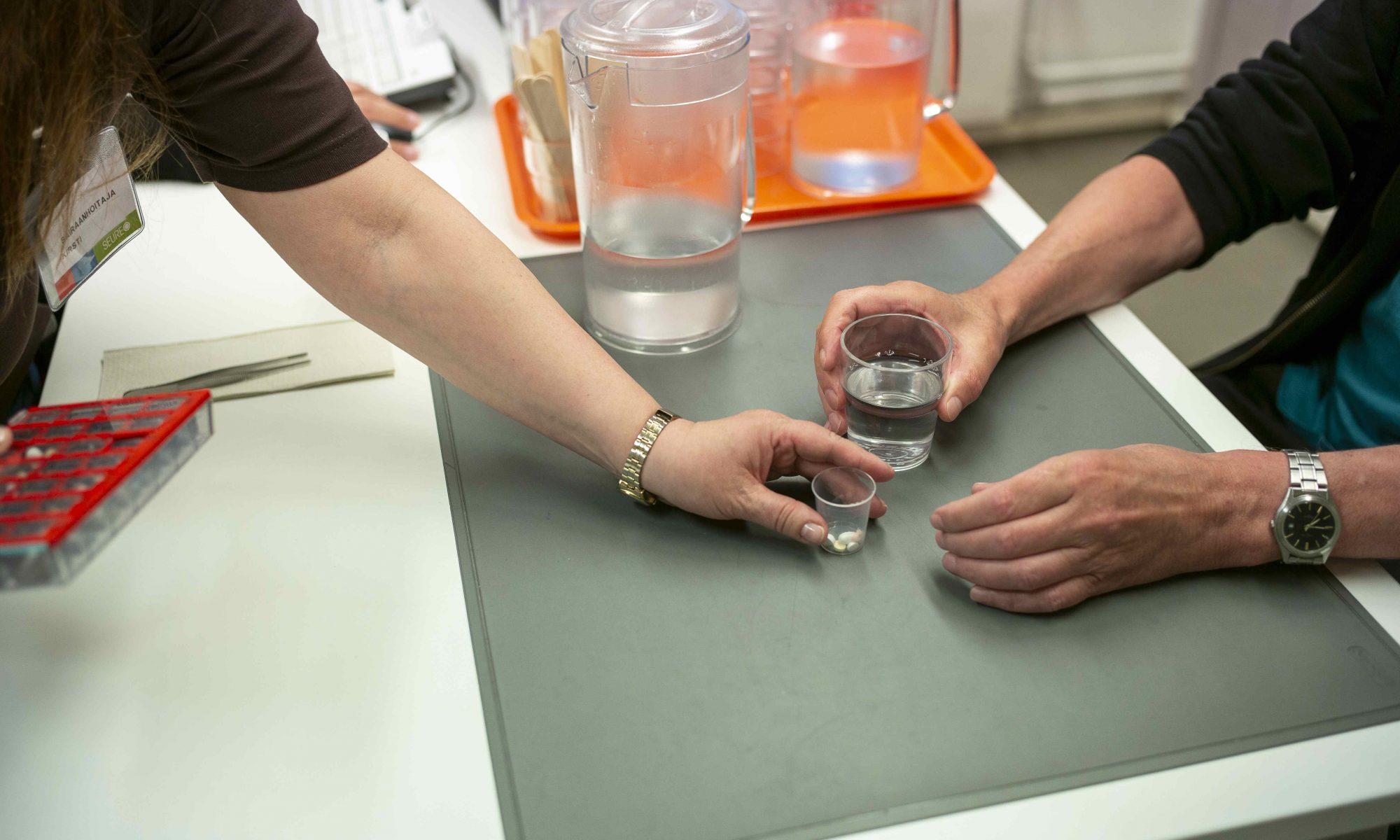 Hoitaja ojentaa vesilasia pitävälle ihmiselle lääkkeet pöydän ääressä