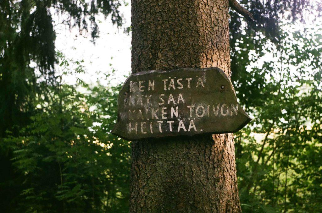 """Puu metsässä. Puuhun on kiinnitetty kyltti, johon on kirjoitettu """"Ken tästä käy, saa kaiken toivon heittää""""."""