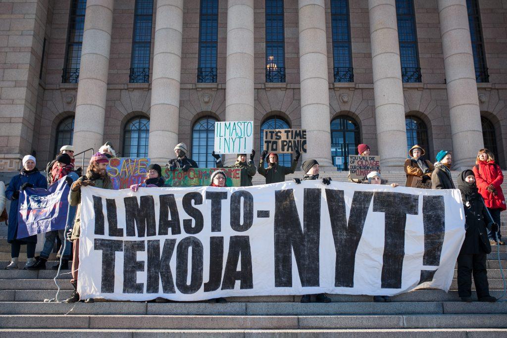 """Henkilöitä mielenosoituksessa Suomen Eduskuntatalon portailla. He pitelevät isoa banderollia, jossa lukee """"Ilmastotekoja nyt!""""."""