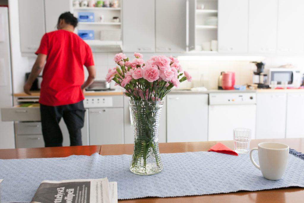 Keittiö, jonka pöydällä on kukkia täynnä oleva maljakko. Taustalla henkilö avaamassa keittiön kaappia.
