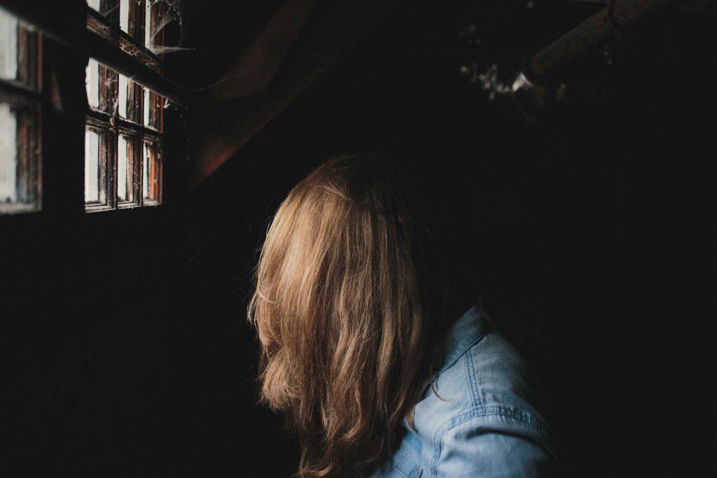 Farkkutakkinen ihminen pimeässä huoneessa, johon tulee valonkajoa ikkunasta