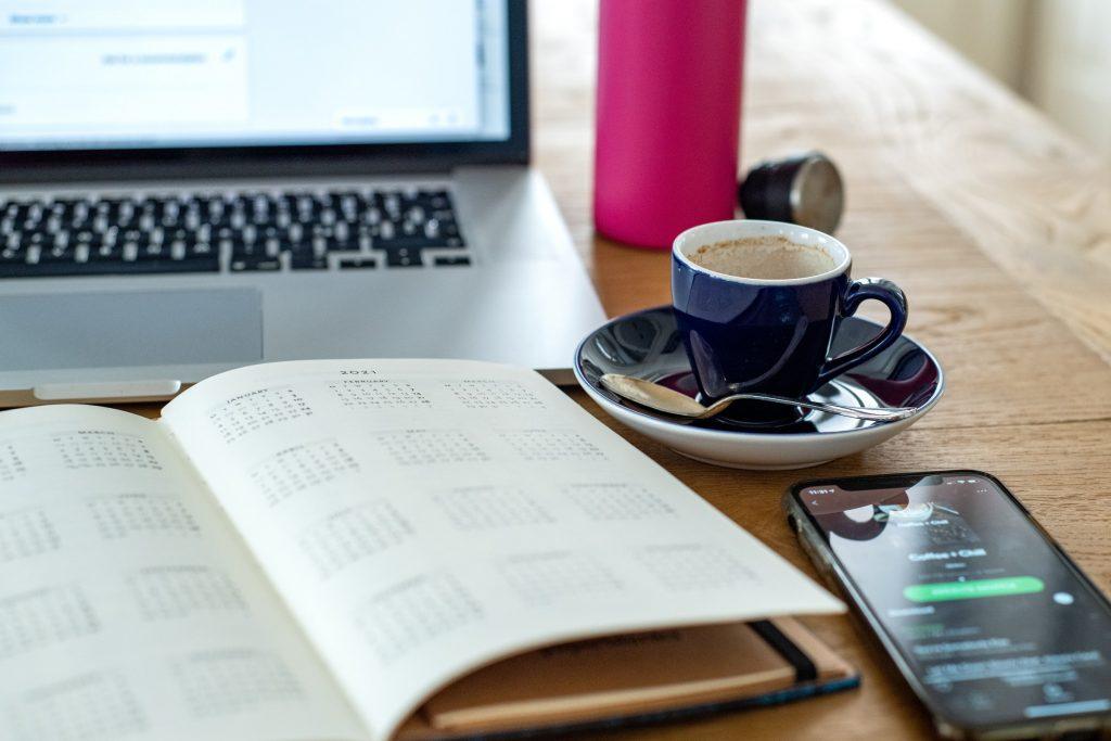 Espressokuppi, kalenteri ja kannettava tietokone kahvilan pöydällä