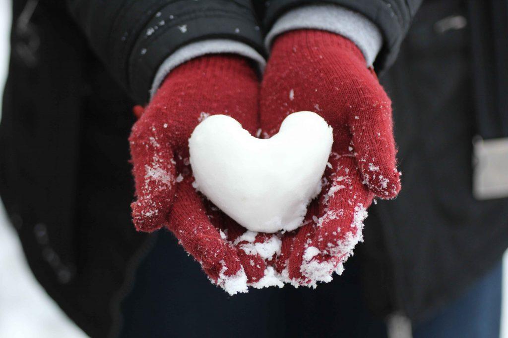 Joku pitelee lapasissaan lumesta muotoiltua sydäntä