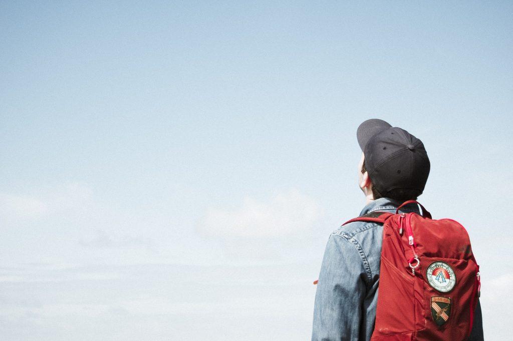 Lippalakkinen henkilö katsomassa kirkkaalle taivaalle reppu selässään.