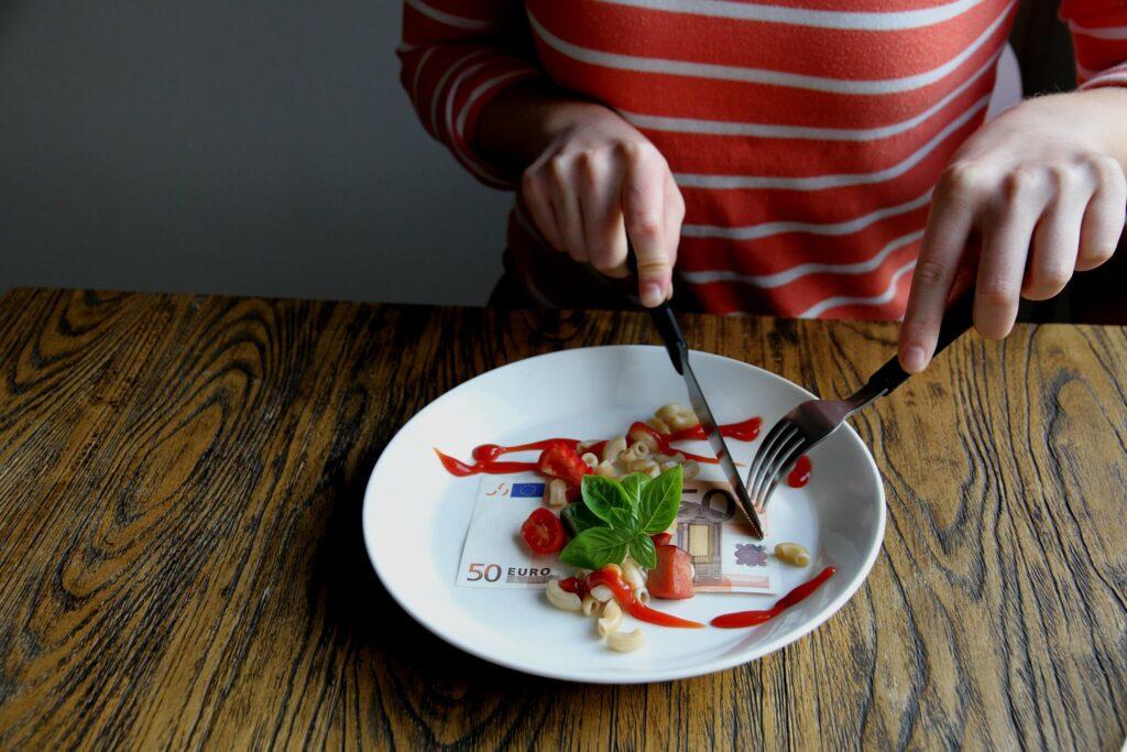Henkilö syömässä haarukalla ja veitsellä. Lautasella on makaroneja, kirsikkatomaatteja, ketsuppia, tuoretta basilikaa ja 50 euron seteli.