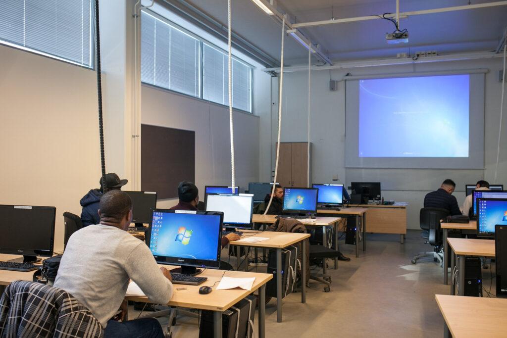 Opiskelijoita ammattikoulun tietokoneluokassa.