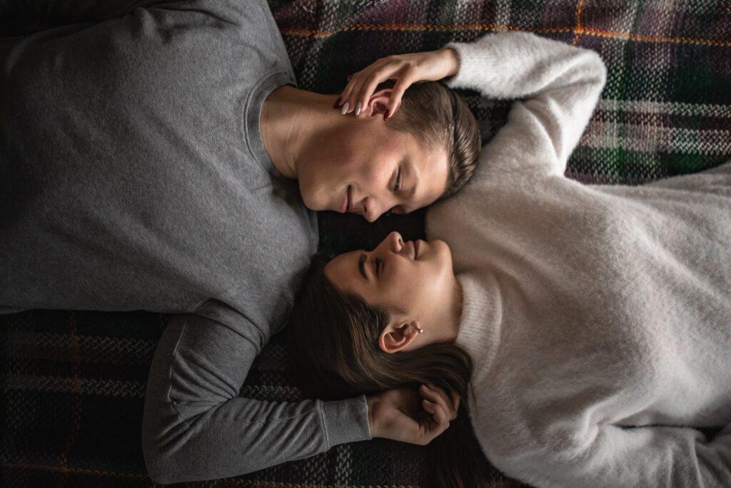 Kaksi henkilöä makaa sängyllä kasvot vastatusten. He hymyilevät ja koskettavat toisiaan.