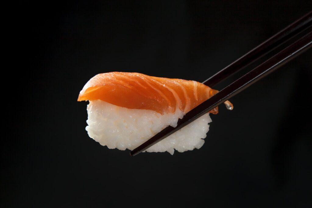 Lohinigiri-sushi mustien syömäpuikkojen otteessa.