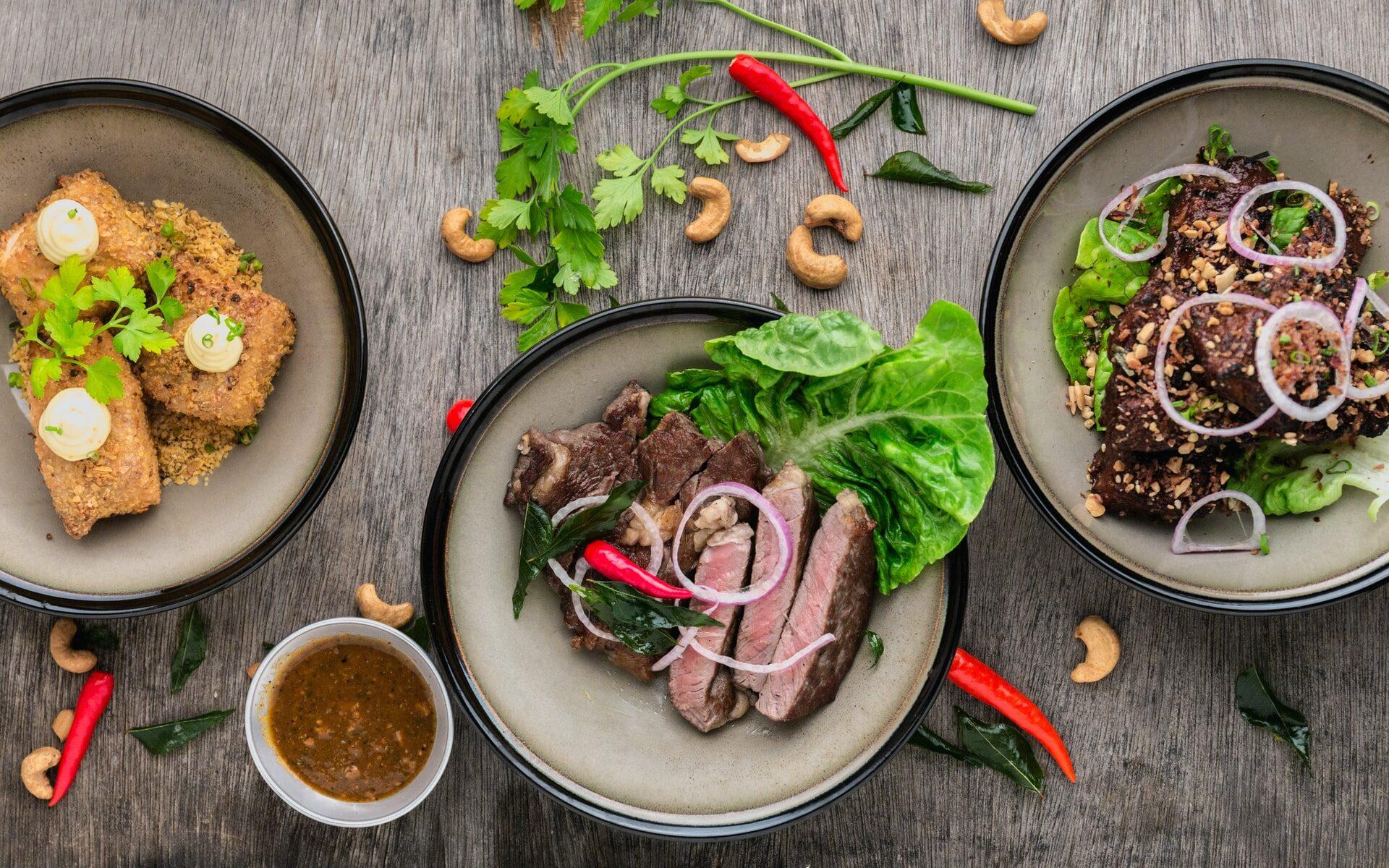 Pöytä, jolla on erilaisia itämaisia ruokia. Pöytälevyn päälle on aseteltu chilipaprikoita, korianteria ja cashewpähkinöitä.