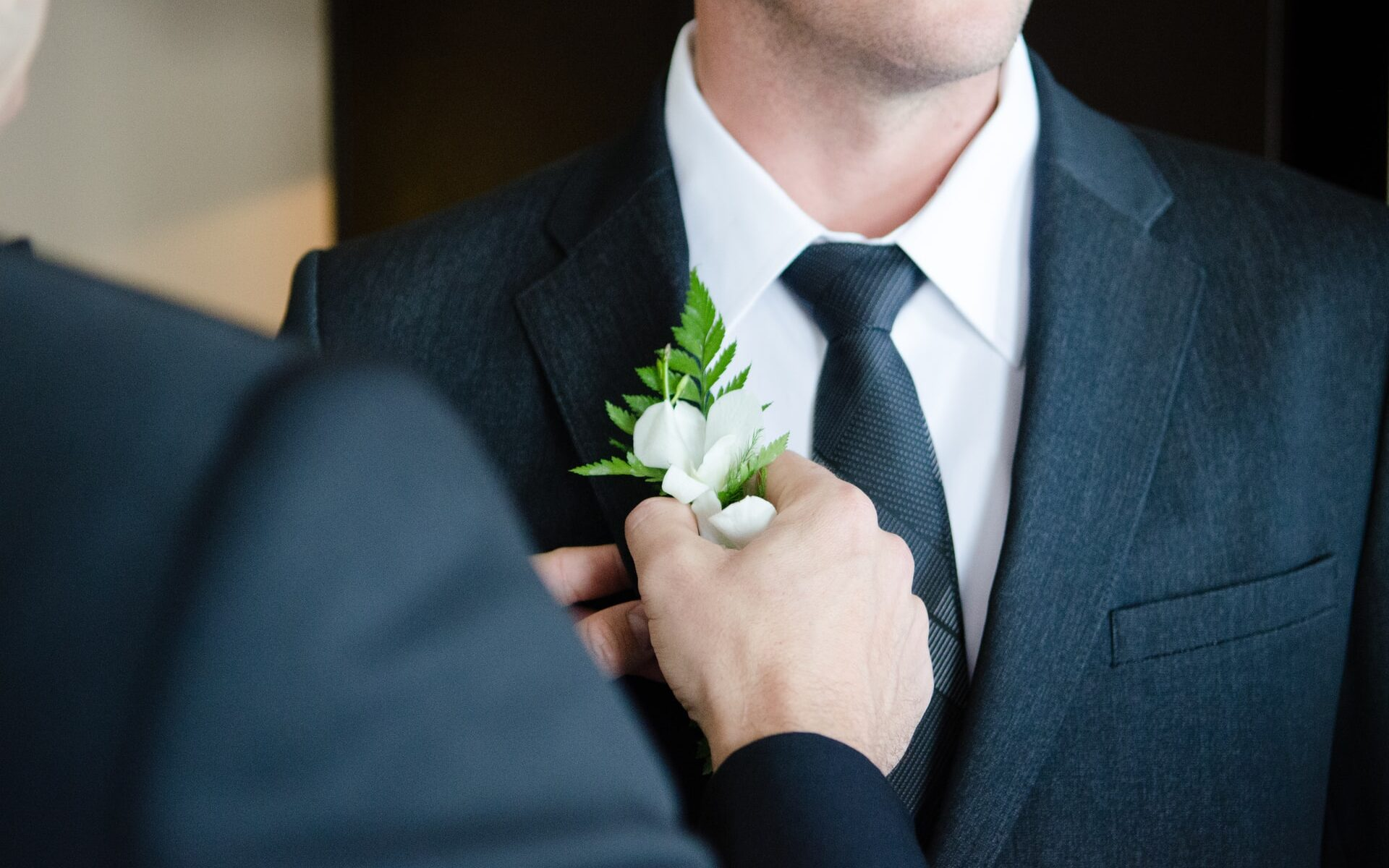 Mustan puvun rintapieleen pujotetaan kukkaa