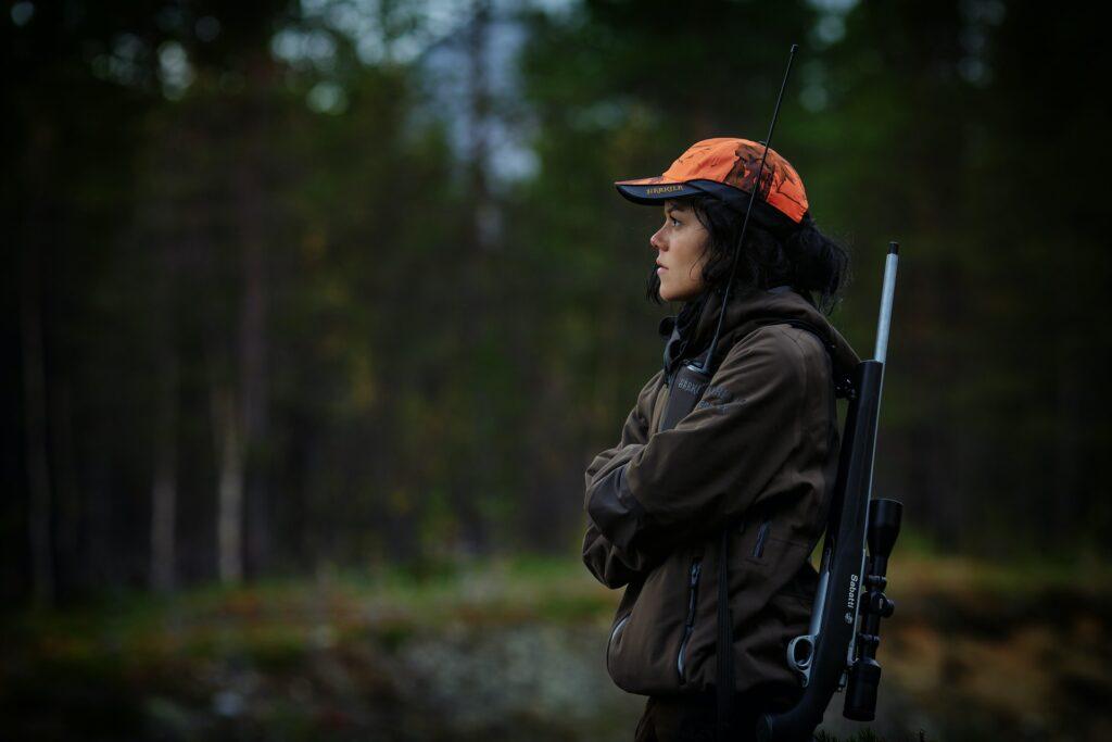 Metsästäjä pimeässä metsässä ase selässään