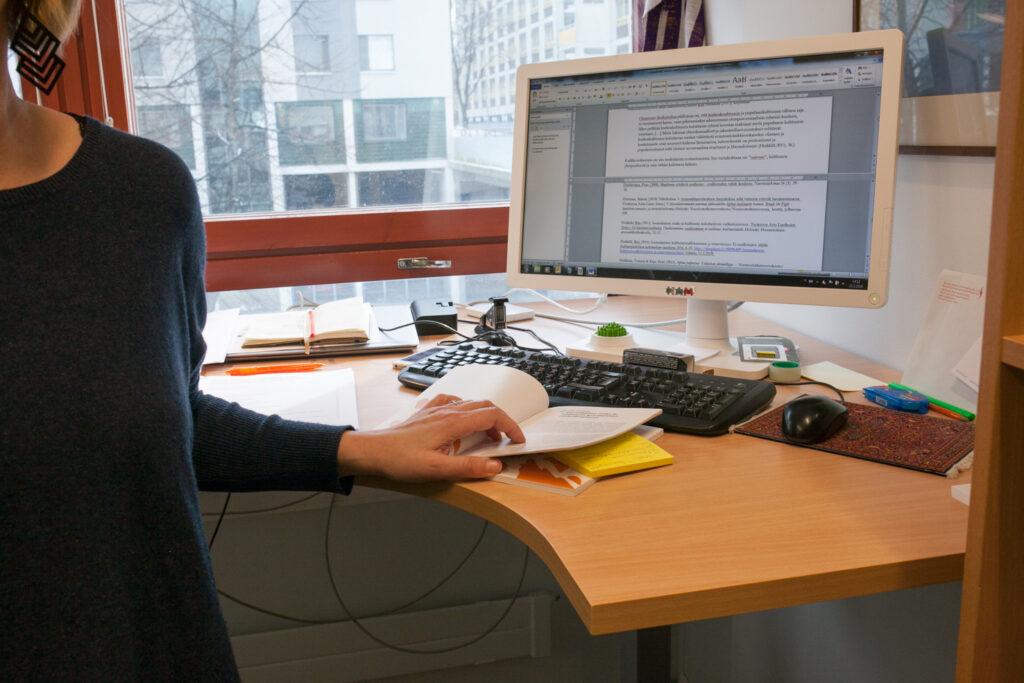 Tutkijan työpöytä, jossa isolla näytöllä on auki tekstinkäsittelyohjelma