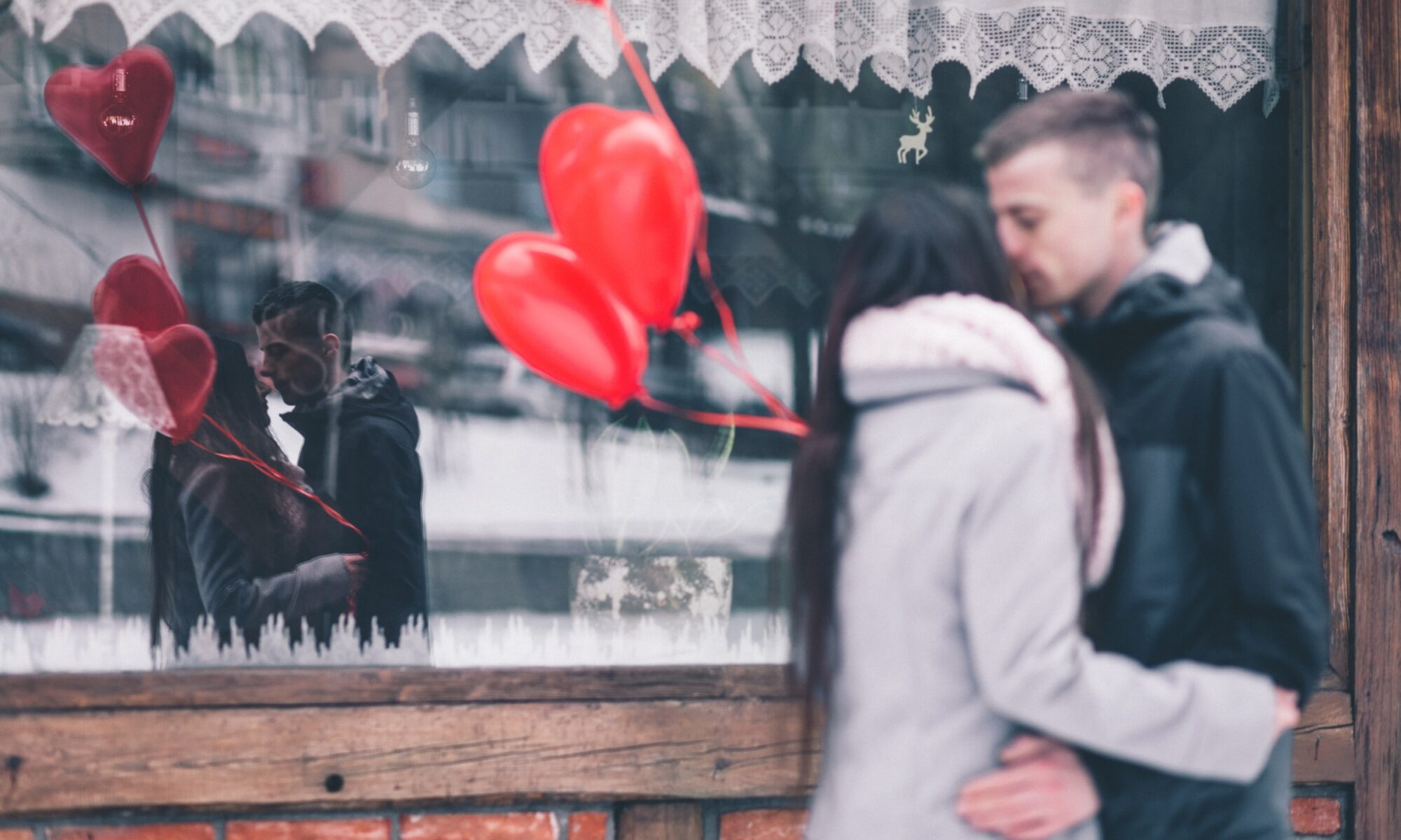 Mies ja nainen suutelevat kadulla punaisten ilmapallojen keskellä, näkyvät myös ikkunan heijastuksessa