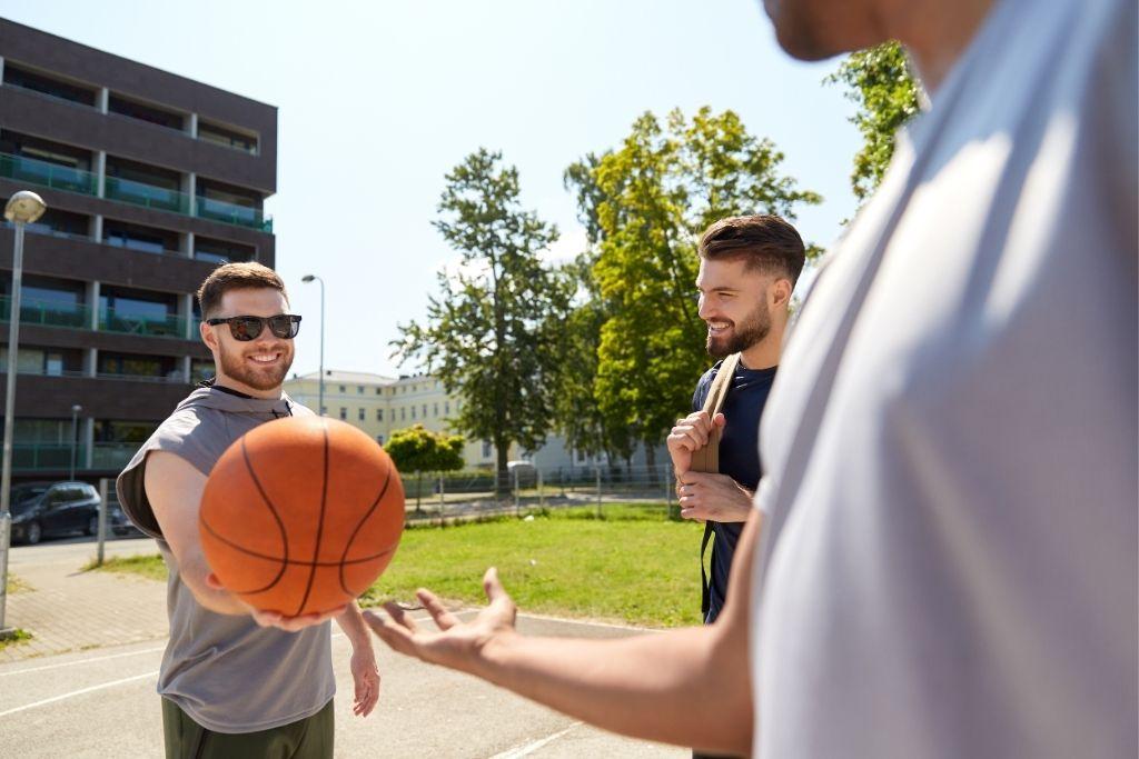 Kolme miestä, joista yksi pitää kädessään koripalloa