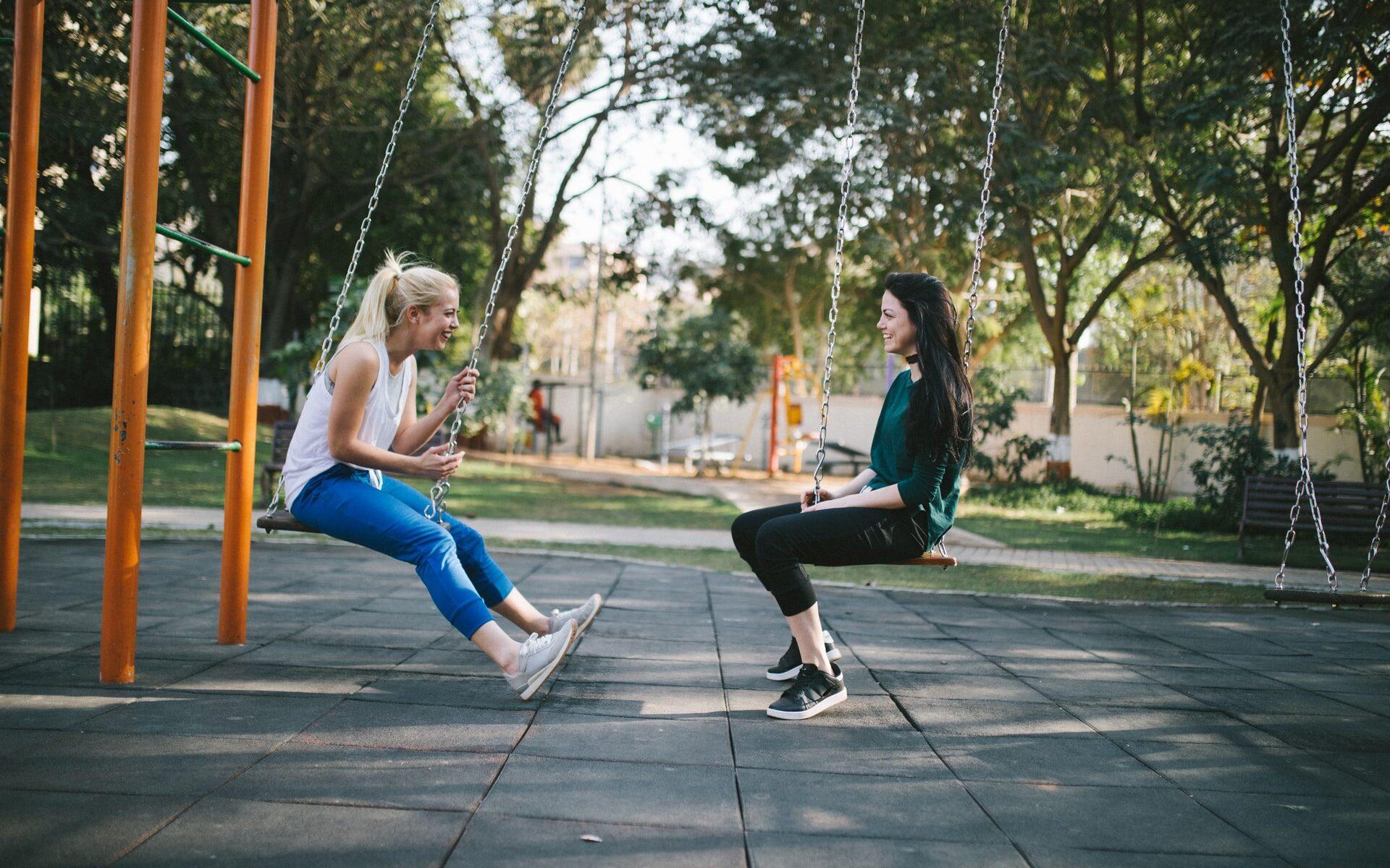 Kaksi naista istumassa leikkipuiston keinuissa kasvotusten