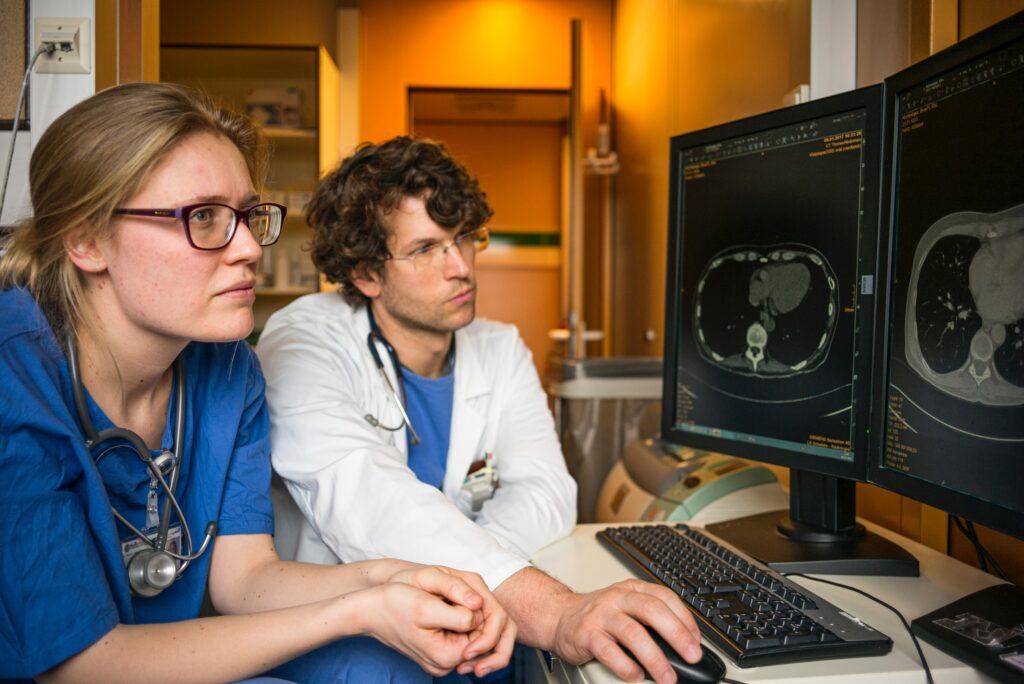 Lääkäri ja sairaanhoitaja katsovat tietokoneen näyttöjä
