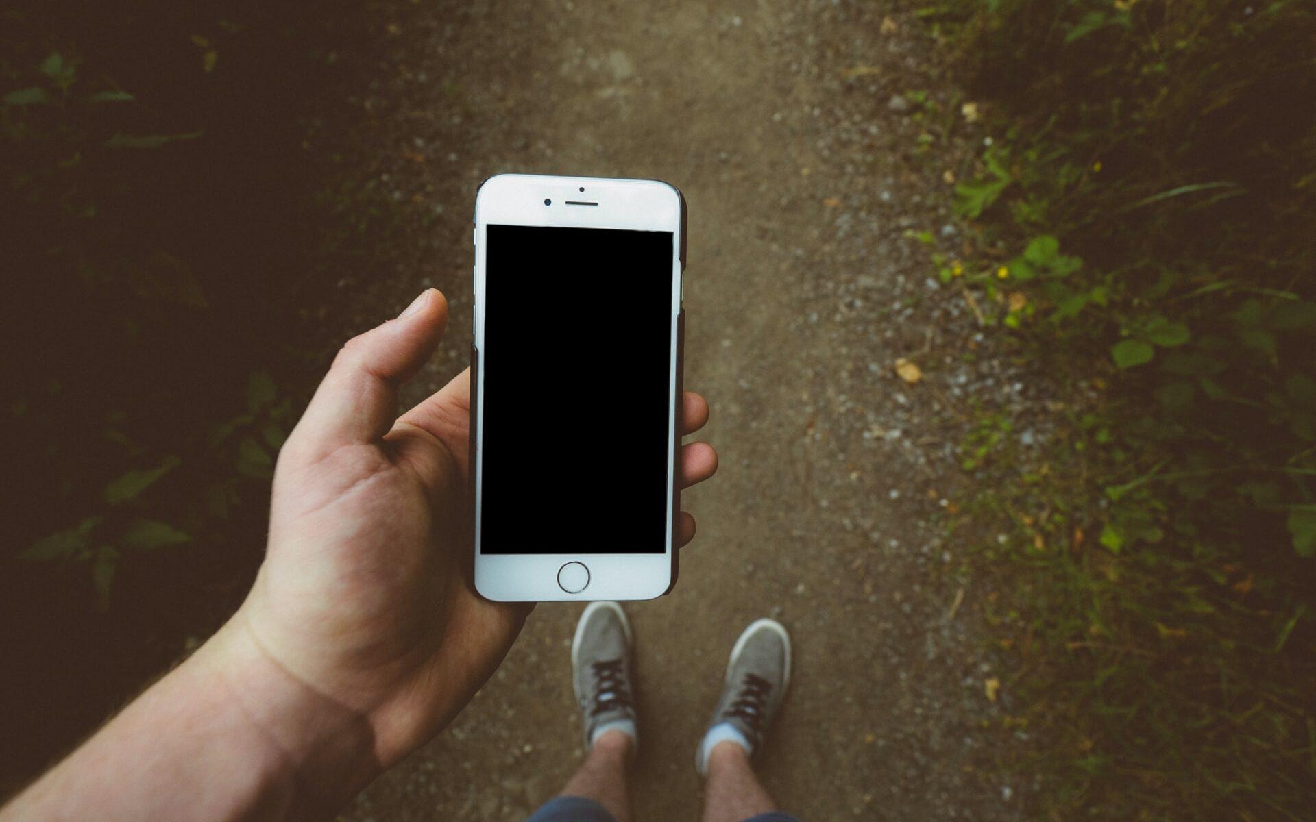 Ihminen puhelin kädessä lenkkipolulla