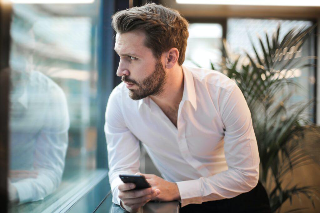 Huolestuneen näköinen mies älypuhelin kädessään