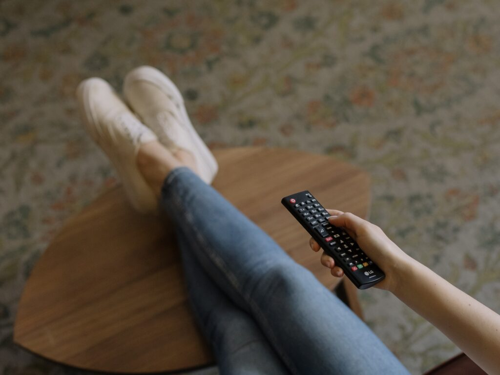 Ihminen pitää TV:n kaukosäädintä kädessään, jalat sohvapöydällä