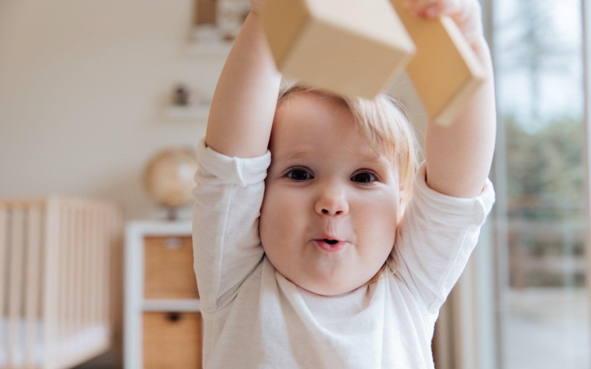 Lapsi heiluttaa lelua