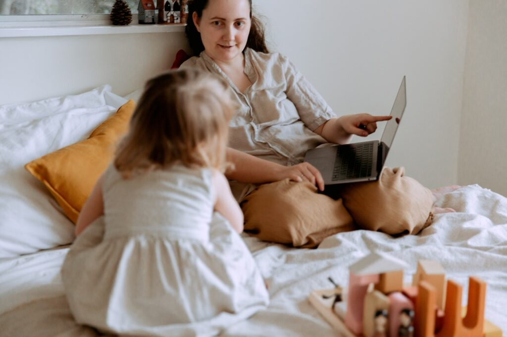 Lapsi ja aikuinen sängyllä. Aikuinen osoittaa lapselle jotain läppärin näytöltä.