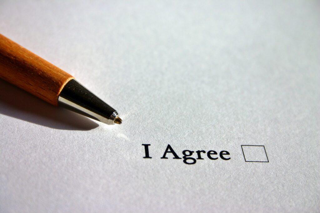"""Paperi, jossa lukee """"I Agree"""". Sen vieressä paperilla on pieni neliö. Paperin päällä on kynä."""