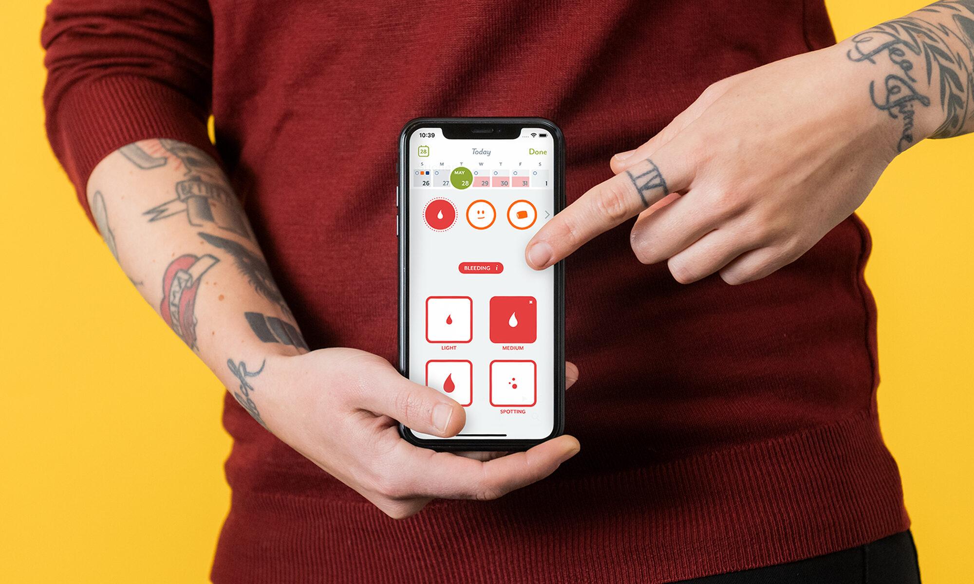 Tatuoitu ihminen pitää kädessään puhelinta, jossa avoinna kuukautissovellus