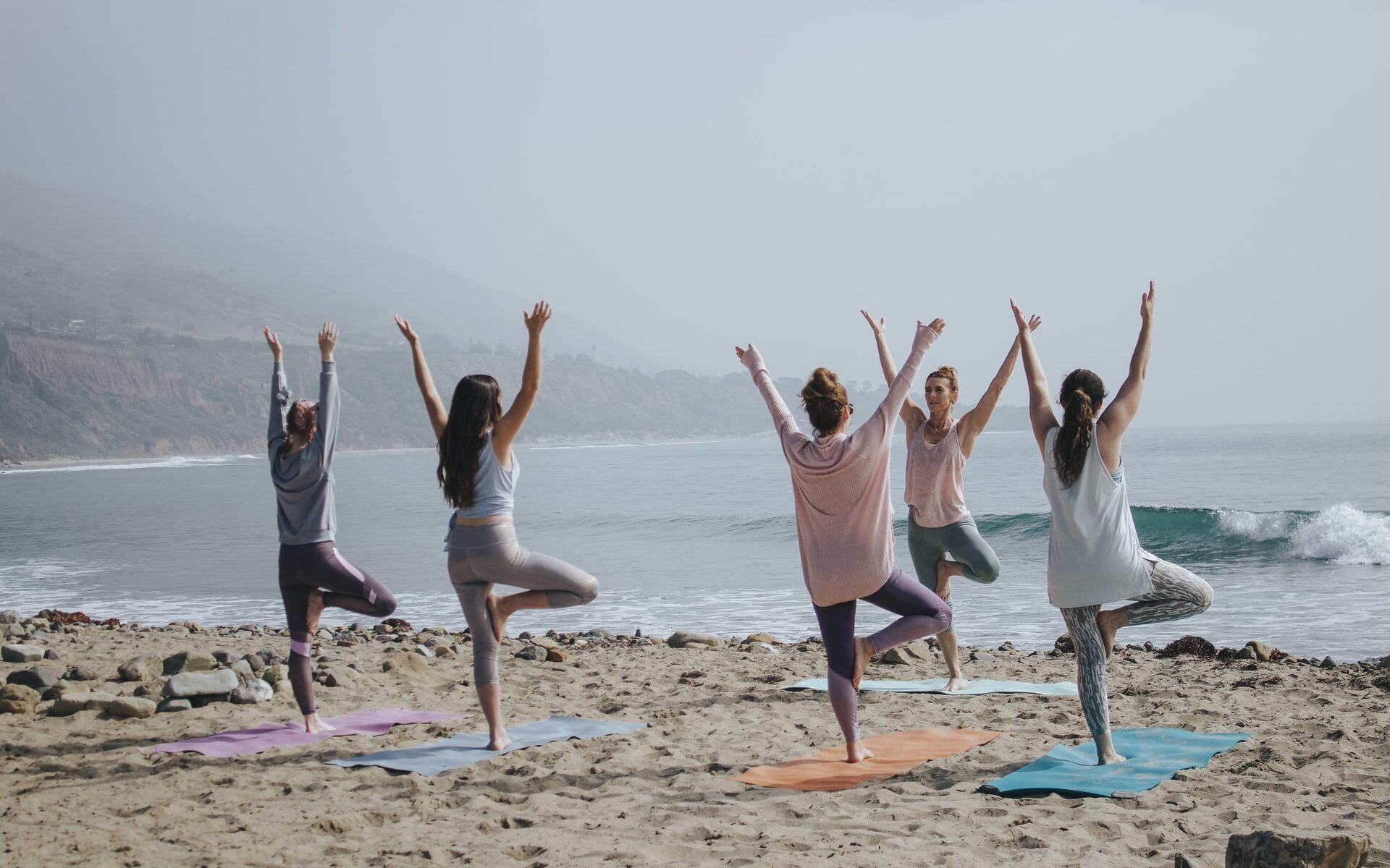 Joukko naisia joogatunnilla merenrannalla