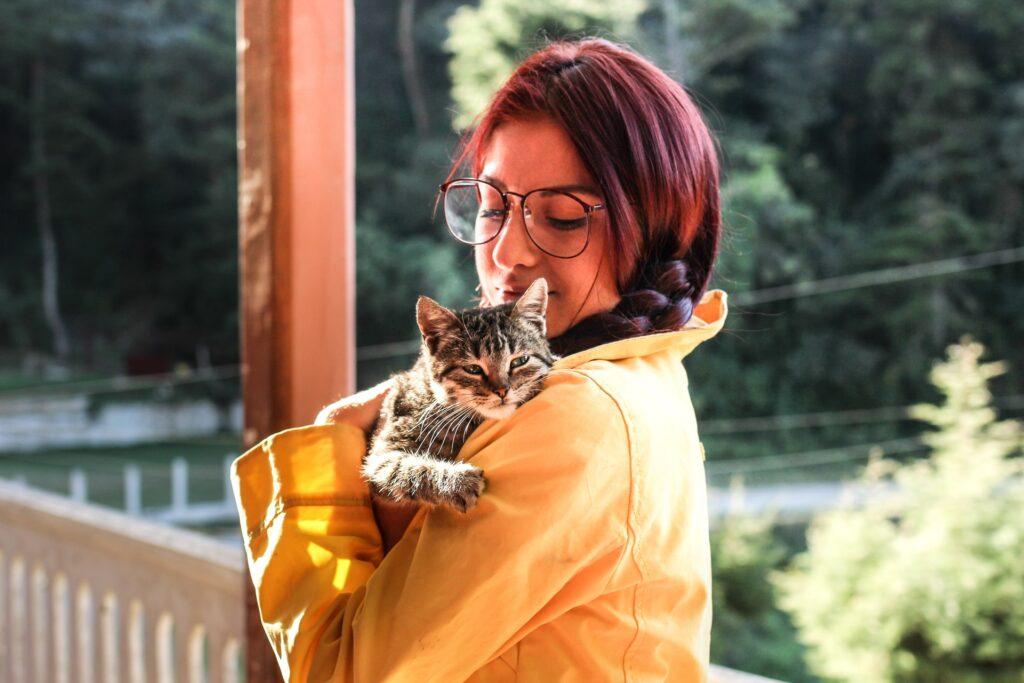 Nainen pitää kissaa sylissään