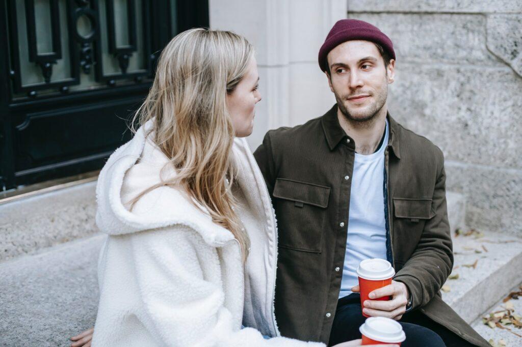 Mies ja nainen istuvat ulkona kahvilla