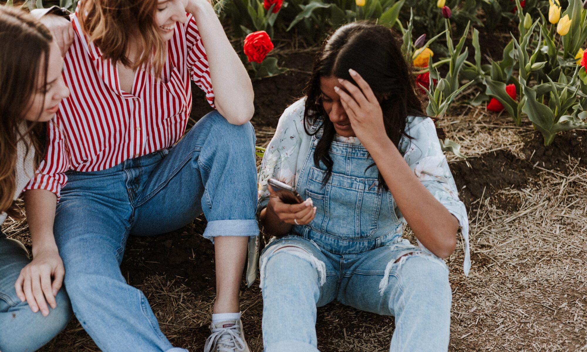 Kaksi tyttöä katsoo, kun kolmas käyttää puhelintaan