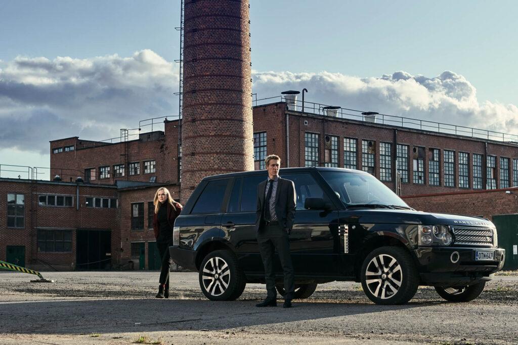 Elokuvan päähenkilö Pasi ja toinen henkilö hienon auton edessä. Taustalla näkyy tehdasrakennus.