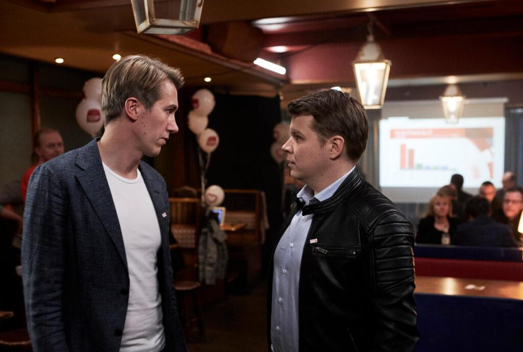 Elokuvan päähenkilö Pasi keskustelee toisen henkilön kanssa tilassa, jossa on vaali-ilmapalloja.