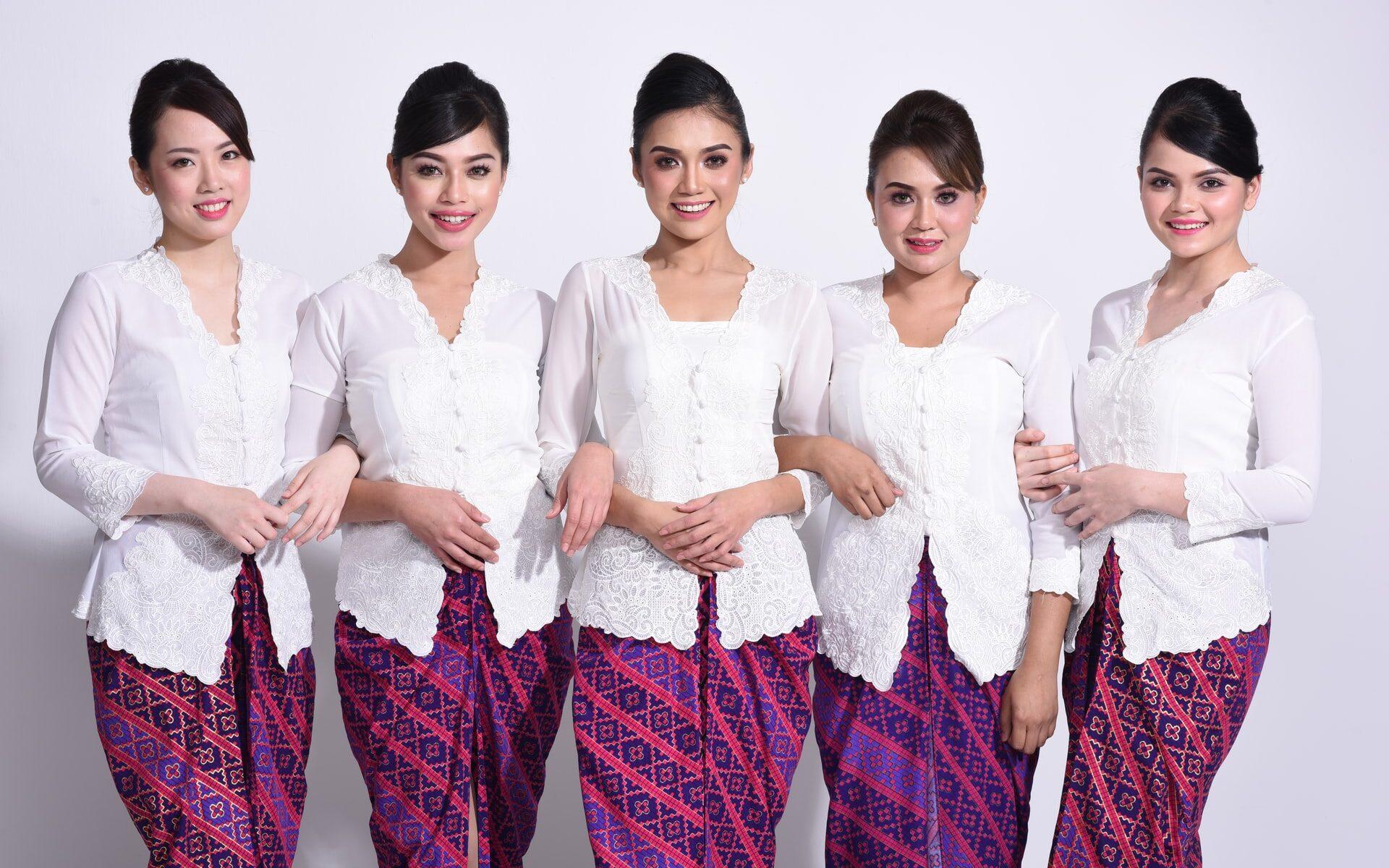 Viisi lentoemäntää seisoo rivissä katsoen hymyillen kameraan. Heillä on kaikilla samanlainen kampaus, meikatut kasvot, valkoiset paidat ja violetit kuviolliset hameet.