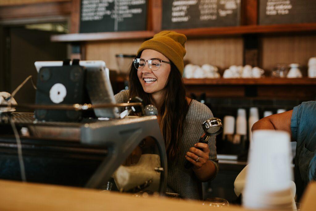 Hymyilevä kahvilan työntekijä.