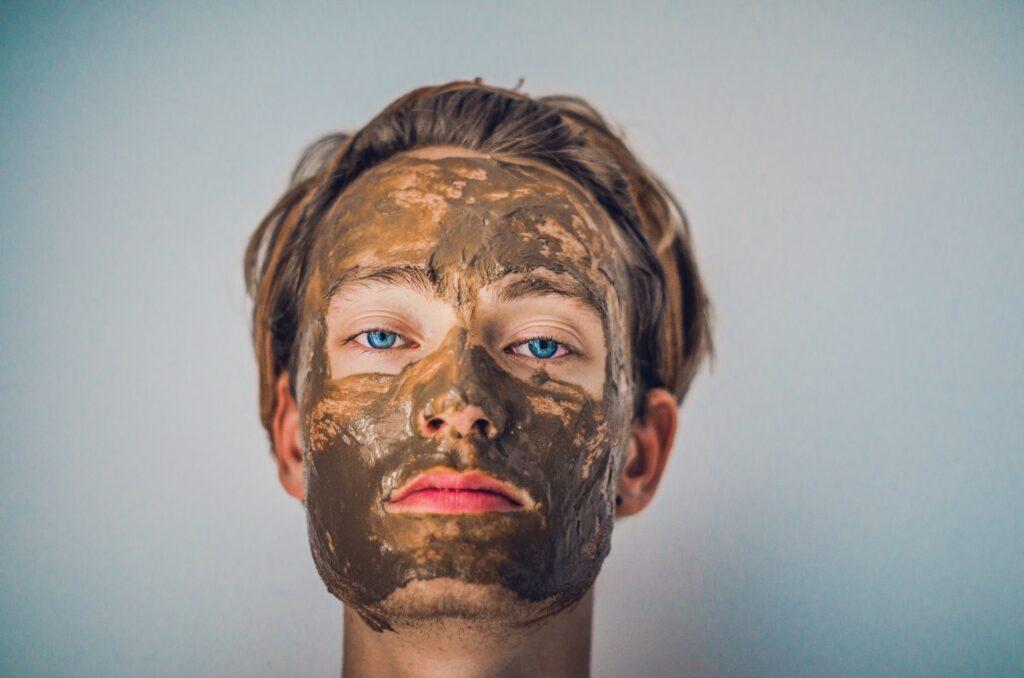 Mieshahmo, jonka kasvoilla on ruskeaa tahnaa. Silmien ympärillä ja huulilla tahnaa ei ole. Hahmolla on vakava ilme.