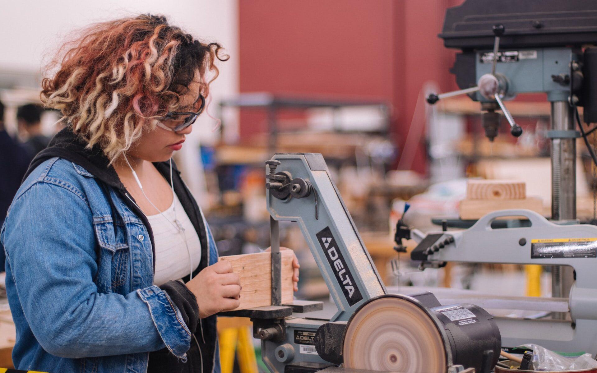 Farkkutakkinen henkilö käsittelee puupalaa teknisen työn tilassa suojalasit päässään.