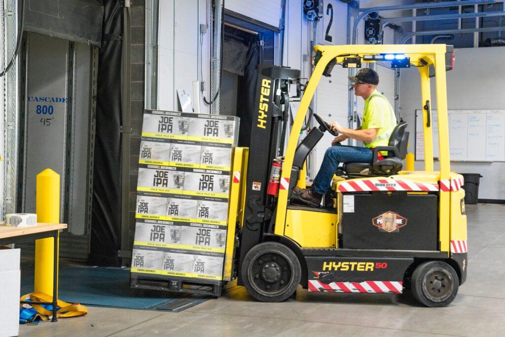 Työntekijä kuljettamassa tavaroita trukilla kuorma-autoon.